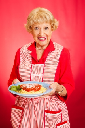 Sweet retro grandmother holding a plate of fresh, hot Italian Spaghetti with marinara sauce.  Red background.
