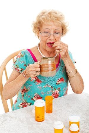 doses: Gezonde senior vrouw die haar dagelijkse doses van de geneeskunde. Witte achtergrond. Stockfoto
