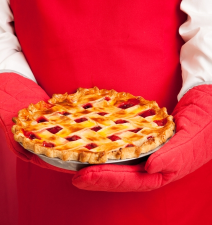 cherry pie: Closeup of a bakers hands in oven mitts,  holding a fresh cherry pie.   Stock Photo