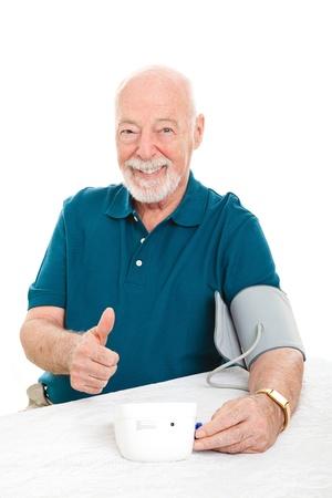 hipertension: Hombre mayor éxito en la reducción de la presión arterial y le da un pulgar hacia arriba signo. Fondo blanco.