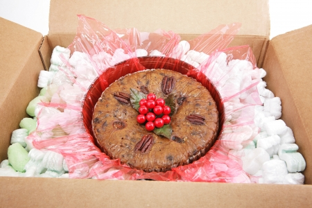 Christmas fruitcake surrounded by packing peanuts, being shipped by mail.   photo