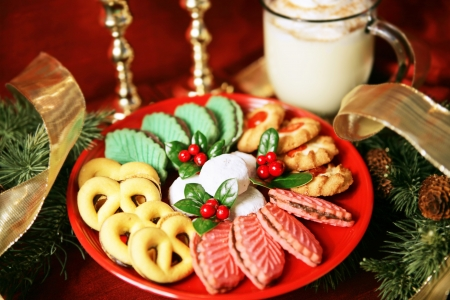 Platter of colorful christmas cookies with eggnog and christmas decorations.  Shallow depth of field with focus on center of cookies.   photo