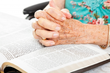 Closeup of senior womans hands on bible, folded in prayer.   photo