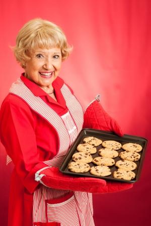 abuela: Abuela ama de casa dulce que sostiene una bandeja de galletas recién horneados de chocolate. Fotografiado delante de fondo rojo. Foto de archivo