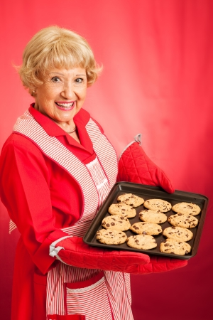 Sweet homemaker grandma holding a tray of fresh baked chocolate chip cookies.  Photographed in front of red background. photo