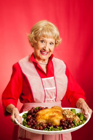 thanksgiving adult: Sweet retro grandmother holding a Christmas or Thanksgiving holiday turkey dinner.  Red background.