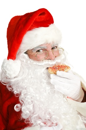 Portrait of Santa Claus eating a Christmas cookie.  White background.   photo