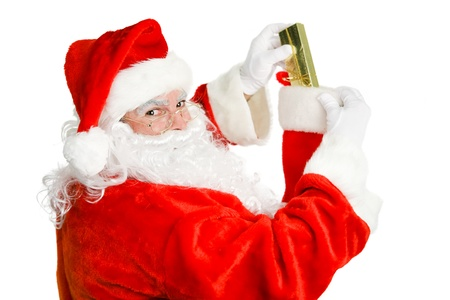 Santa Claus stuffing a christmas stocking.  Isolated on white.  photo