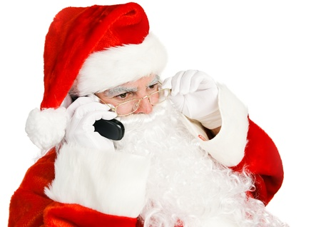 st  nick: Santa Claus takes telephone call on his land line.  Isolated on white.