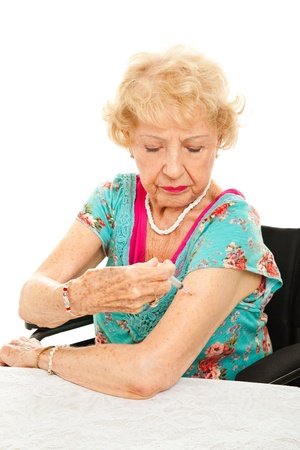 Senior woman giving herself an injection for diabetes, arthritis, etc.  White background.   photo