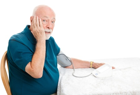 Senior man taking his blood pressure and shocked by the results.  White background. Stock Photo - 16144059