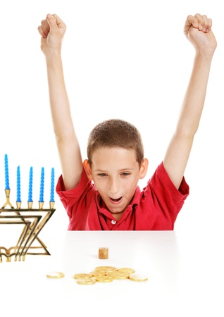 Little boy playing with his dreidel on Hanukkah.   White background.   photo