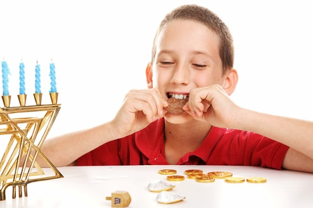 Little boy playing dreidel and eating chocolate Hanukkah gelt.  White background.   photo