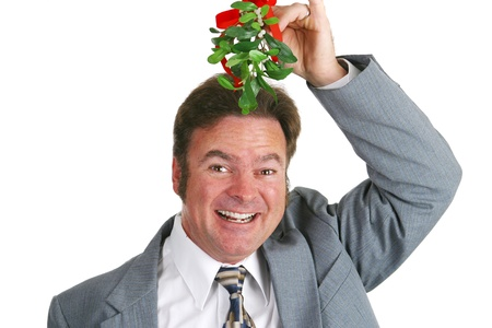 Friendly businessman under the mistletoe, hoping for a kiss.  Isolated on white.   photo