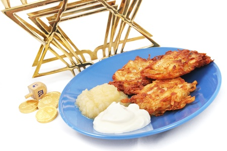 gelt: Plate of potato pancakes, a dreidel and Hanukkah gelt, and a menorah on white.