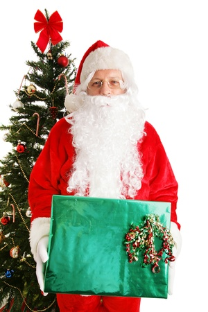 Santa Claus standing by the Christmas tree holding a shiny present.  White background.   Stock Photo - 16604348