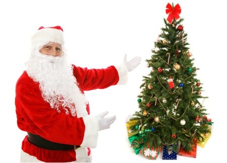Santa Claus with his arms out presenting a decorated Christmas tree. Composite image. Stock Photo - 16604202