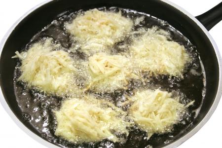 Potato latkes for Hanukkah, frying in oil.   photo