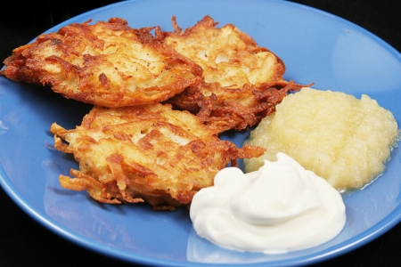 Potato latkes for Hanukkah, served with sour cream and applesauce .   photo