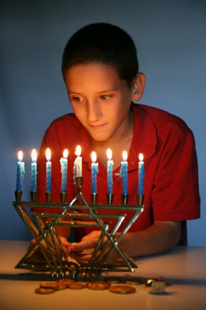 Young boy looking at the Hanukkah menorah, illuminated only by its light.   photo