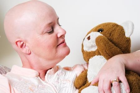 canc�rologie: Patients atteints de cancer, chauve de la chimioth�rapie, re�oit le confort de tenir un ours en peluche.
