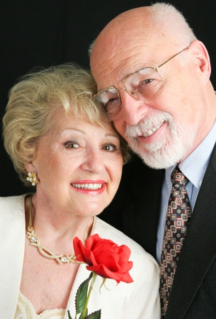Elegant senior couple dressed up in their finery, and holding a Valentines Day rose.   photo
