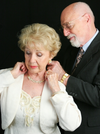 Senior man helping his wife put on a beautiful diamond necklace he has given her as a gift.   photo