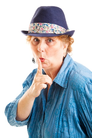 Middle aged woman puts her finger to her lips in a quiet or secret gesture.  Isolated on white.   Stock Photo