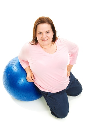Full body isolated view of a pretty, overweight woman with a pilates ball.