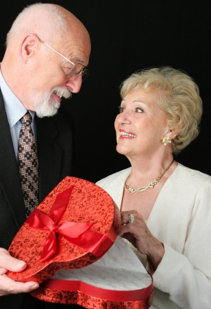 black satin: Handsome senior man gives valentines day chocolates to his beautiful wife.   Stock Photo