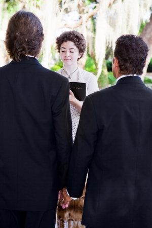 christian marriage: Young female minister marries male couple in lovely outdoor wedding ceremony.