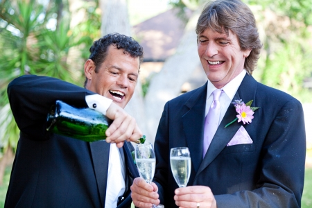 homosexual partners: Gay couple pouring champagne to toast at their wedding.  The groom on the right is covered with champagne from the splash when the cork popped.   Stock Photo