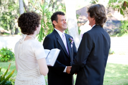 christian marriage: Gay male couple gets married by a young female minister in a beautiful outdoor wedding ceremony.