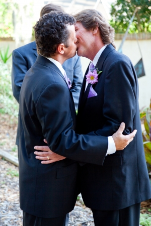 Handsome gay couple kissing at their marriage ceremony.   photo