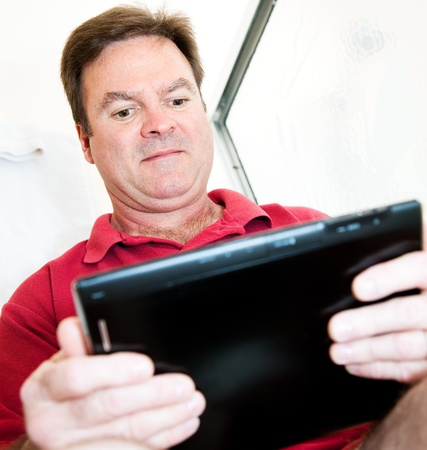 bowel movement: Man in the bathroom using a tablet PC while on the toilet.   Stock Photo