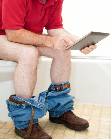 Man sitting on the toilet using his tablet PC. photo