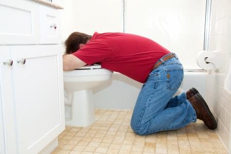 L'homme à genoux dans la salle de bain, des vomissements dans les toilettes. Banque d'images