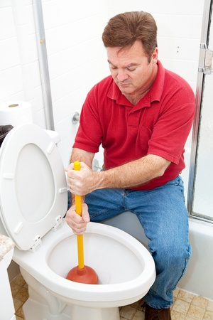 Man using a plunger to unclog the toilet.   Stock Photo - 17260715