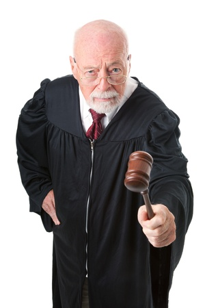 No nonsense, skeptical old judge banging his gavel. Isolated on white. Banco de Imagens