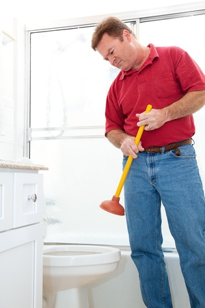 Man in bathroom holding a plunger but reluctant to plunge the toilet. Stock Photo - 17260719