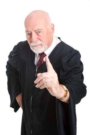 lays down: Stern old judge wags his finger as he lays down the law.  Isolated on white.