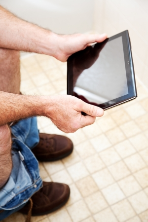 Man using a generic tablet PC while he goes to the bathroom. Stock Photo - 17286021