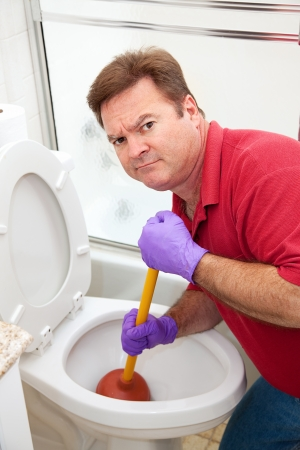 toilet bowl: Man is not happy about having to use a plunger to unclog the toilet.