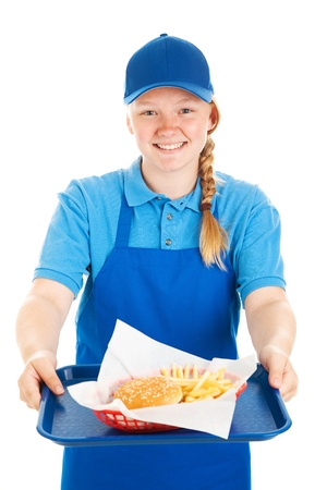 Friendly teenage fast food worker serving a burger and fries meal with a smile   Isolated on white