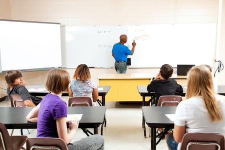 Afro-américain enseignant de sexe masculin enseigne une classe diversifiée de mathématiques école
