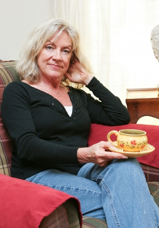 middle age women: Beautiful mature blond woman relaxing at home with a cup of coffee or tea    Stock Photo
