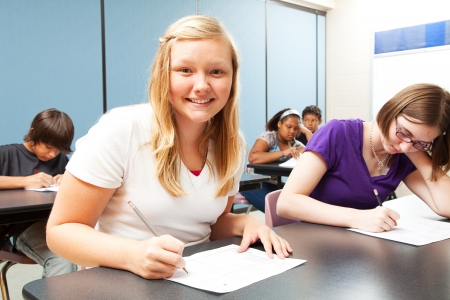 blonde minority: Pretty blond girl sitting in her high school class    Stock Photo