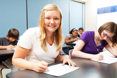 Pretty blond girl sitting in her high school class    Stock Photo