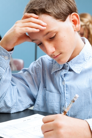 Cute adolescent school boy concentrates while taking a standardized test