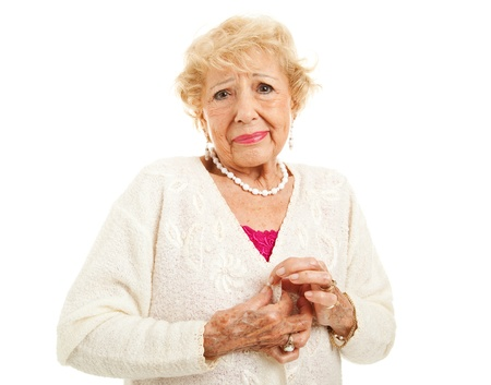 Senior woman with arthritis is having trouble buttoning her sweater  Isolated on white Stock Photo - 18351387